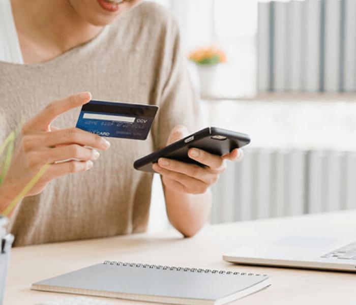 Mujer sosteniendo una tarjeta de crédito con una mano, y un celular con el otro, mientras revisa los datos de su cuenta en su celular.