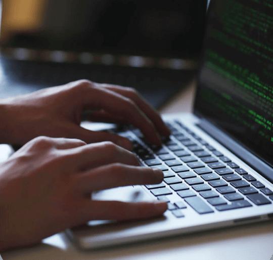 Close up de un par de manos teclenado código en una computadora