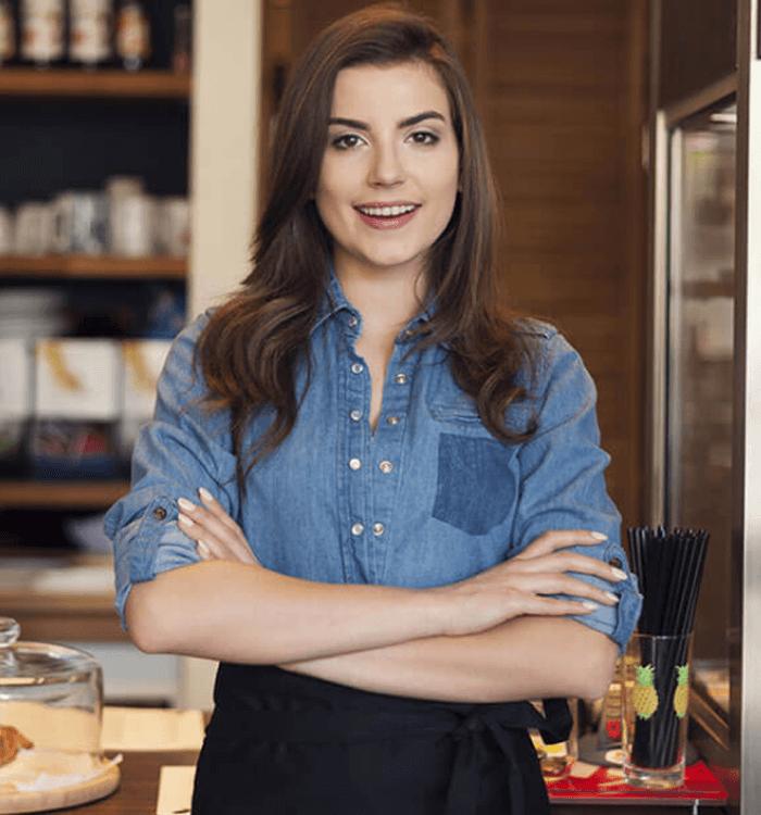 Fotografía de una mujer sonriente y empoderada que esta cruzada de manos mientras al fondo se ve un negocio de pasteles.