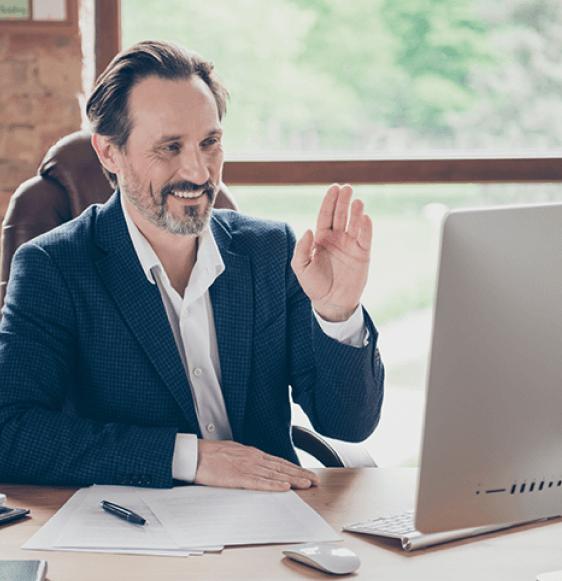 Hombre de negocios de edad madura sosteniendo una videoconferencia en su computadora y saludando con la mano izquierda.