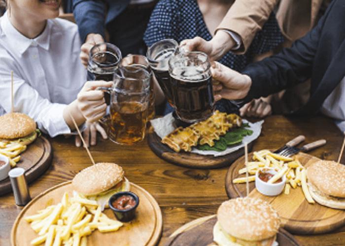 Grupo de amigos conviviendo alrededor de una mesa llena de alimentos y brindando con cervezas.