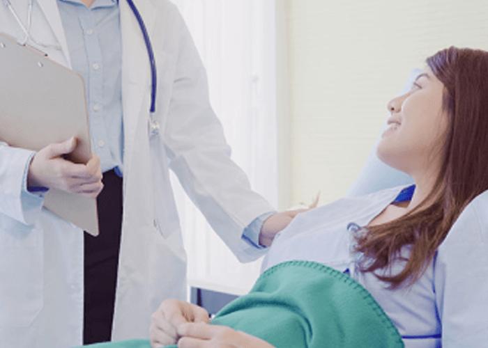 Paciente mujer recostada en la cama de un hospital que mira sonriente a su médico.