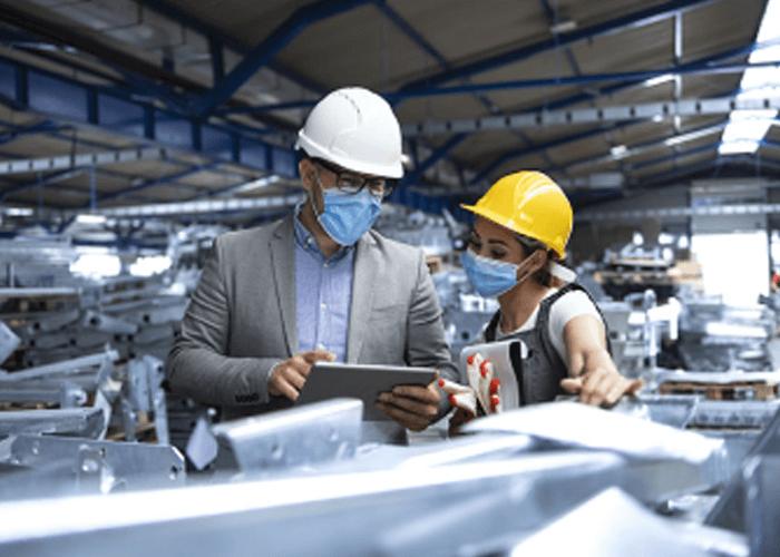 Dos empleados hombre y mujer al interior de una bodega llena de materiales de metal, observando un ipad con datos.