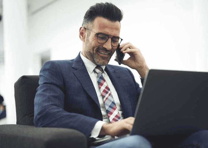 Hombre conversando por su celular mientras teclea en su laptop