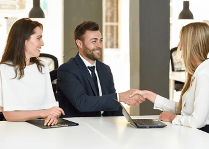 Dos personas hombre y mujer sentados en una oficina, vestidos con traje y estrechando un apretón de manos con una ejecutiva.