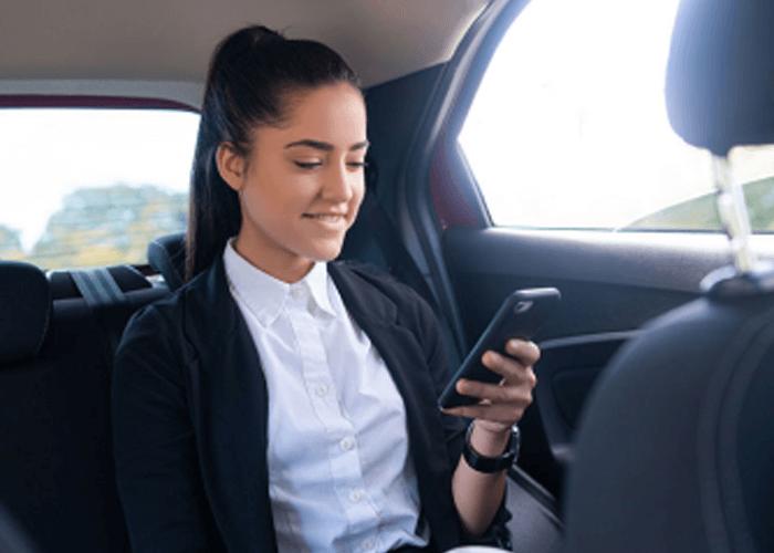 Mujer al interior de un taxy confortable mientras revisa sonriente su celular.